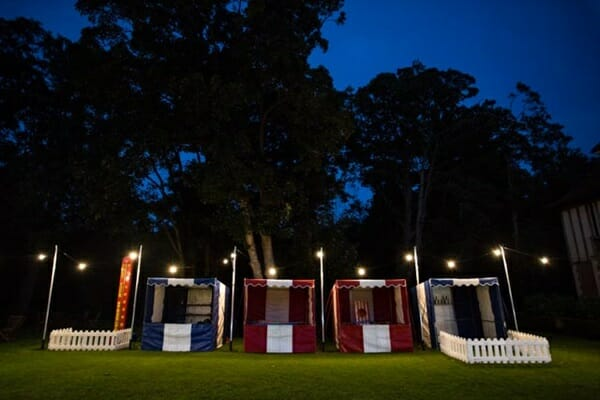 Funfair stalls with festoon lighting.